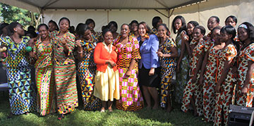 Bridget Sisney (orange sweater) and Usha Satish (periwinkle jacket), ambassadors from the Black College Fund, pose with the Africa University Choir during a break in the 20th anniversary celebration.